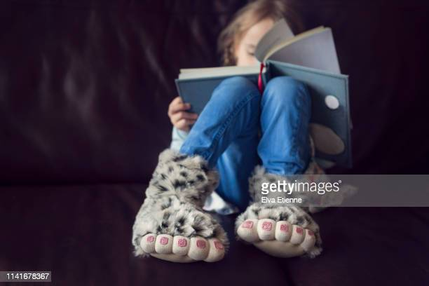 child wearing novelty monster feet slippers, reading a book - スリッパ ストックフォトと画像