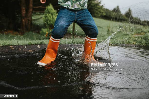 child wearing orange wellies jumping in a deep puddle - wellington boot stock pictures, royalty-free photos & images