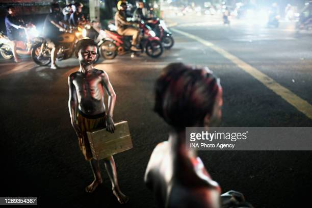 Child wearing silver paint on the body, also known as 'Silverman' is seen begging for money on a street in Jakarta amid the coronavirus pandemic.
