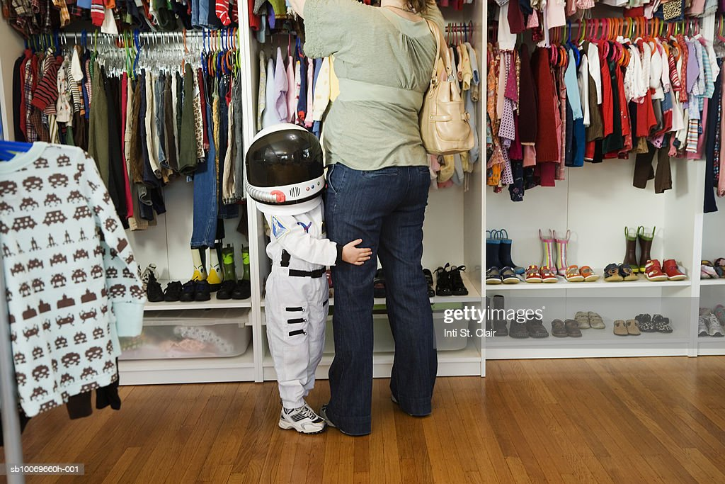 Child (4-5 yeras) wearing space costume hugging mother's leg in shop : Stock-Foto