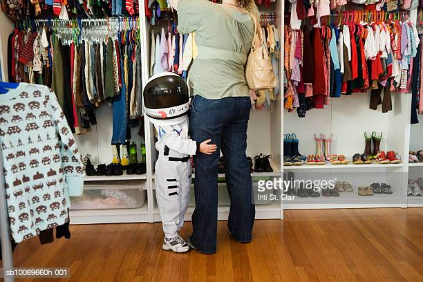Child (4-5 yeras) wearing space costume hugging mother's leg in shop