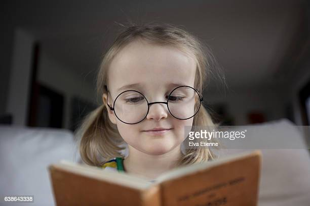 child (3-4) wearing specatcles and reading book - girl nerd hairstyles stock photos and pictures