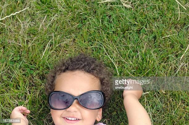 Child wearing sunglasses lying on grass having fun