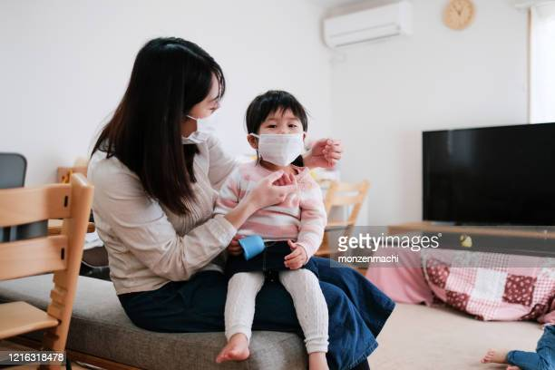 感染症を予防するために外科用マスクを着用している子供 - 予防 ストックフォトと画像
