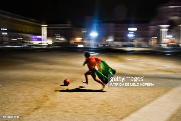 A child wearing the Portuguese national football team dribbles a ball at Terreiro do Paco Square in Lisbon on June 22 2014 during a public viewing of...
