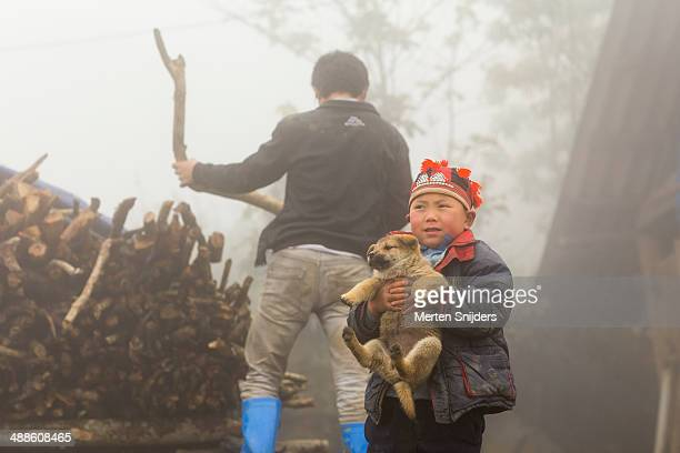 child wearing tribal hat with dog - merten snijders ストックフォトと画像
