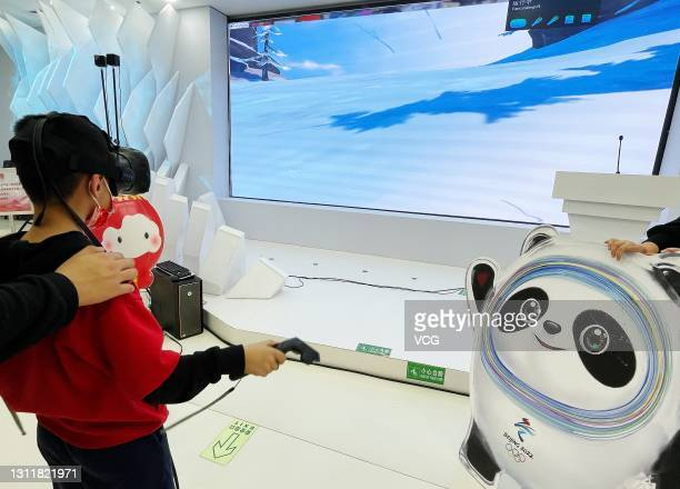 Child wearing VR glasses plays a skiing game at the Beijing 2022 licensed product flagship store to mark the 300-day countdown to the opening of the...