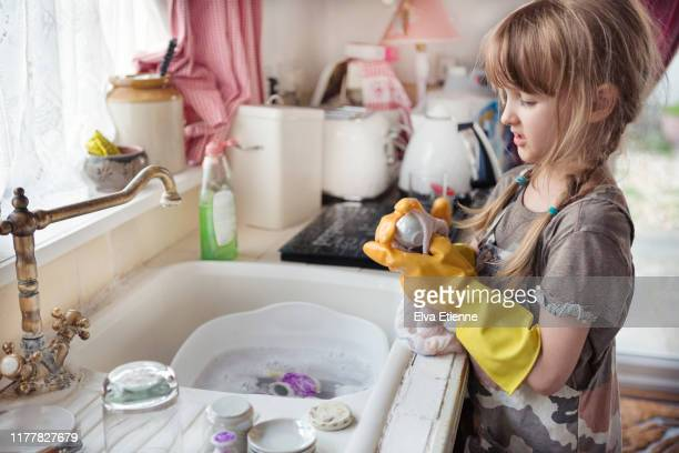 child (6-7) wearing washing up gloves and washing dishes in a kitchen sink - kids with cleaning rubber gloves stock pictures, royalty-free photos & images