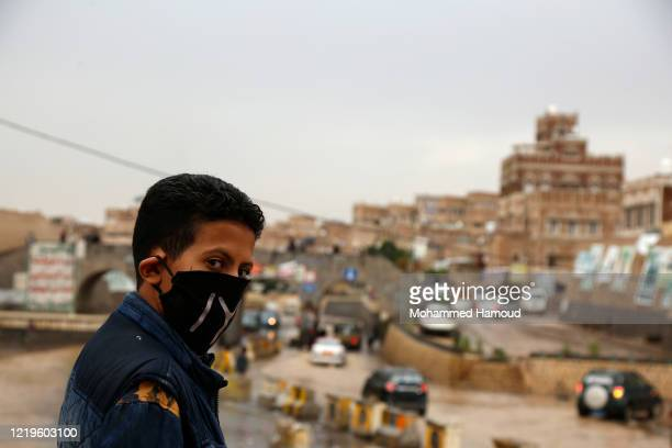 Child wears a facemask as he stands in front of historic buildings of Old Sana'a on April 18, 2020 in Sana'a, Yemen.