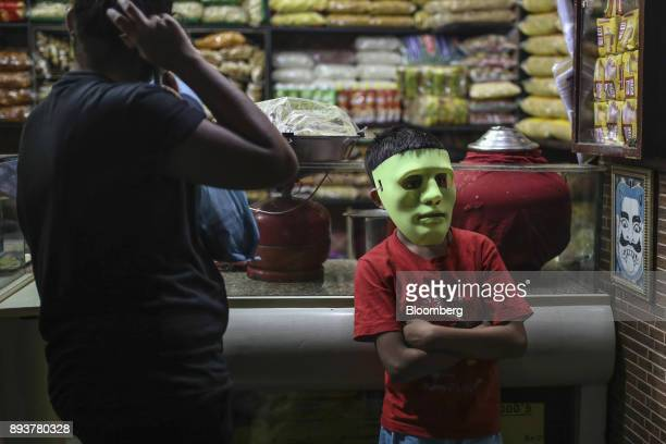 A child wears a green costume mask at a store in Mumbai India on Friday Dec 15 2017 India's inflation surged past the central bank's target...