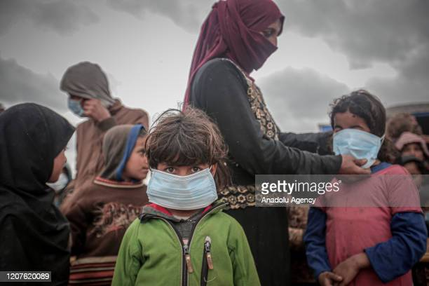 Child wears a mask as a preventive measure against coronavirus as Idlib Health Directorate and Civil Defense Crews along with local charities carry...
