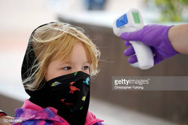 A child wears a mask as she has her temperature checked at the entrance to Alton Towers on July 4 2020 in Alton England The popular theme park...