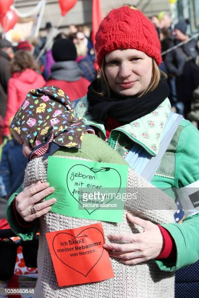 A child wears a piece of paper on it's back which reads 'born through the help of a freelance midwife' during a rally for more security for freelance...
