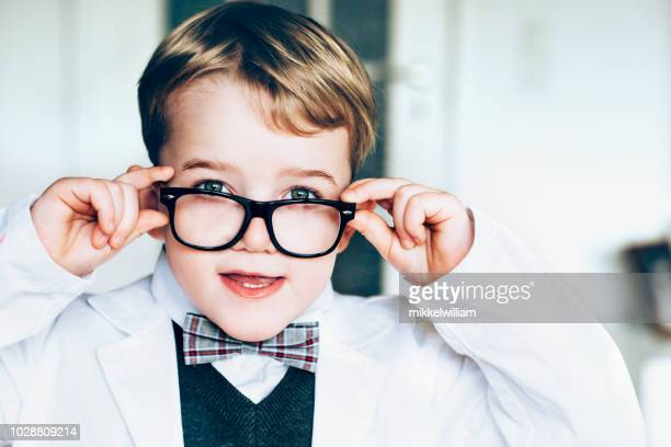 Child wears lab coat and big glasses and looks like a scientist