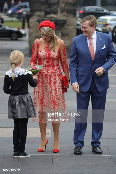 A child welcomes King WillemAlexander of The Netherlands with Queen Maxima of The Netherlands upon their arrival at the Porta Nigra a magnificent...