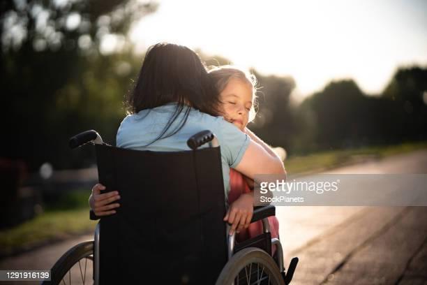 車椅子で母親を抱きしめる子供のホイット目は閉じた - 麻痺 ストックフォトと画像
