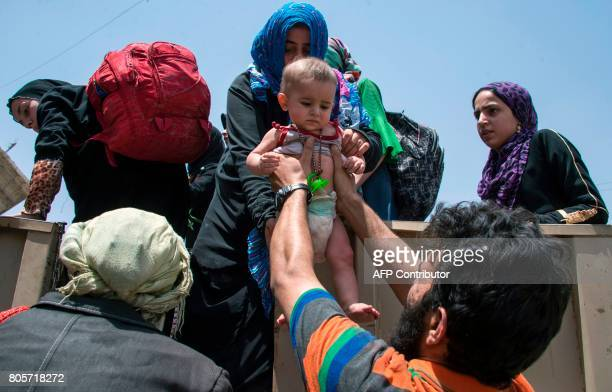 A child who fled the fighting in the Old City of Mosul is handed over to a woman on a vehicle in the city's western industrial district awaiting to...