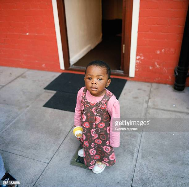 A child whose parents are recent immigrants from Africa outside her family flat on the Kingsmead estate in Homerton in the eastern part of Hackney...