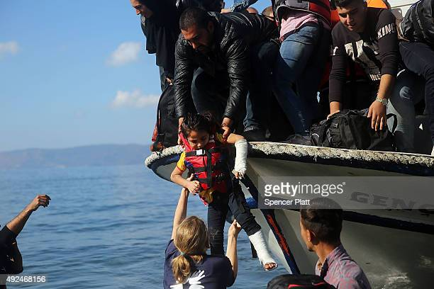 A child with a broken arm and leg is helped as she arrives with other Syrian and Iraqi refugees onto the island of Lesbos from Turkey on October 13...