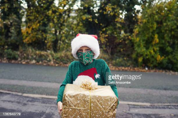 child with a christmas present - sally anscombe stock pictures, royalty-free photos & images