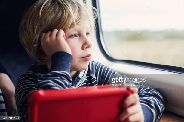 child with a digital tablet looking out of a train window - menino loiro olhos azuis imagens e fotografias de stock