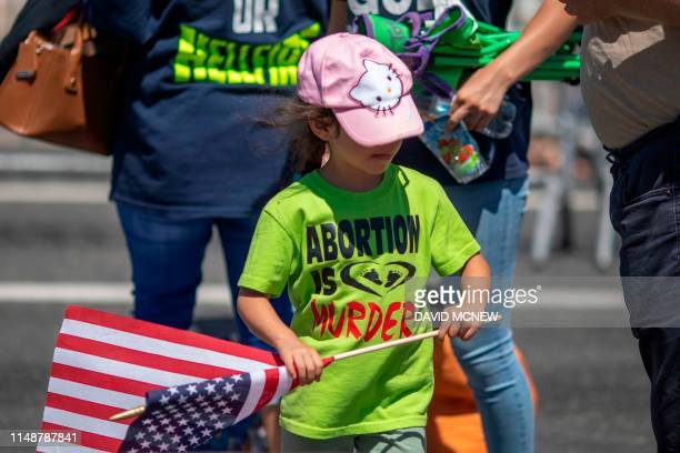 Child with an anti-LGBTQ evangelical Christian group wears an anti-abortion shirt and carries an American flag during the annual LA Pride Parade in...