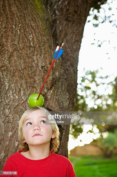 Child with apple and arrow on head