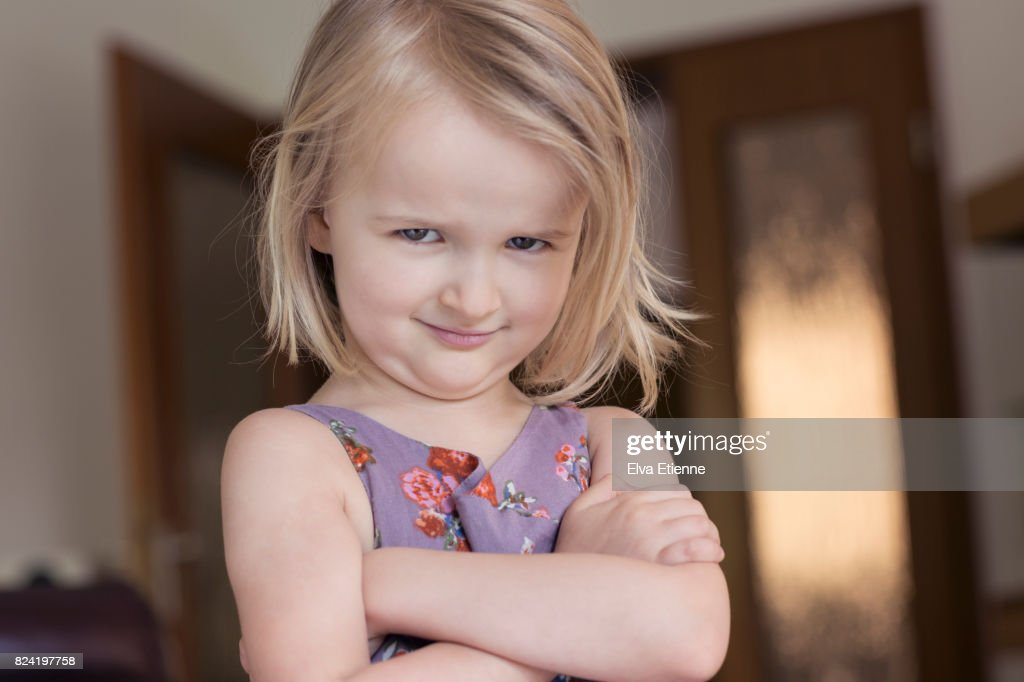 Child (4-5) with arms folded and glaring, bossy facial expression : Stock Photo