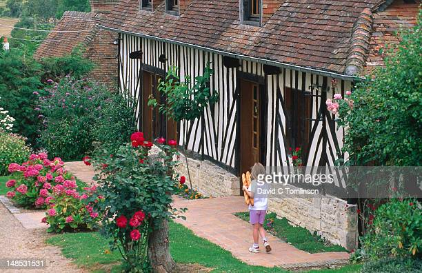 child with baguettes in front of half-timbered cottage. - calvados stock pictures, royalty-free photos & images