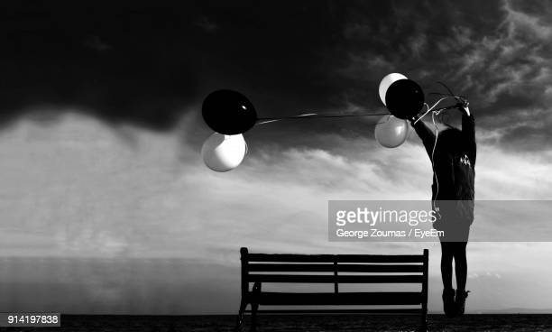 Child With Balloons Standing Against Cloudy Sky