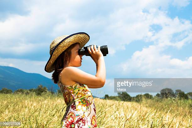 Child with binoculars in a wheat field