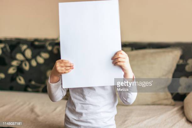 child with blank paper - placard stock pictures, royalty-free photos & images