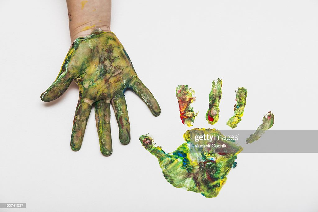 Child with colorful painted hand beside her hand print on paper : Stock Photo