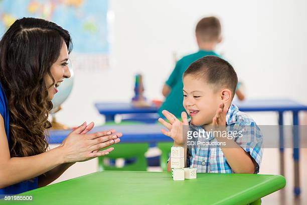 child with down syndrome clapping, playing with blocks in classroom - learning disability stock pictures, royalty-free photos & images