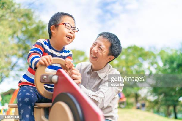child with down syndrome enjoying with his father at public park - disability stock pictures, royalty-free photos & images