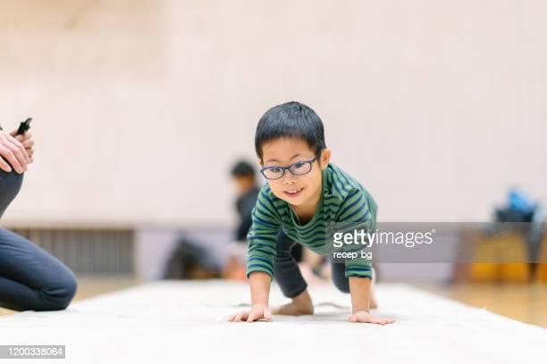 kind mit down-syndrom übt gymnastik mit instruktor - turner syndrome stock-fotos und bilder
