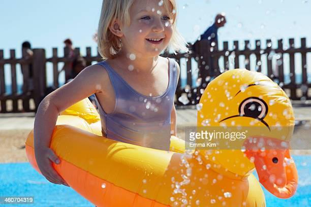 child with duck-shaped float in pool - emma white stockfoto's en -beelden