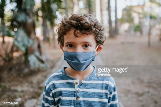 kind met gezichtsbeschermingsmasker - normaal nieuw concept - alleen één jongen stockfoto's en -beelden