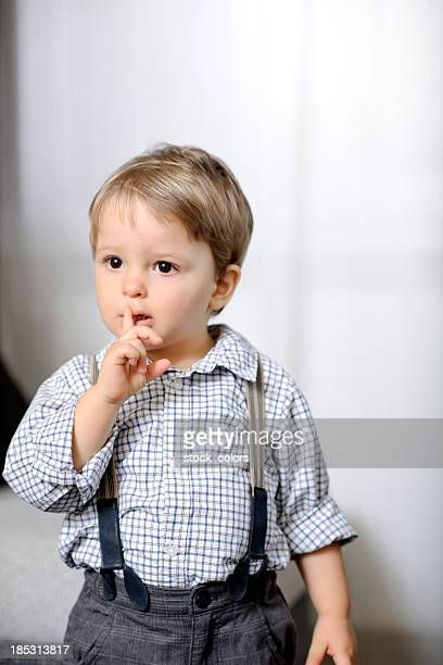 child with finger on lips