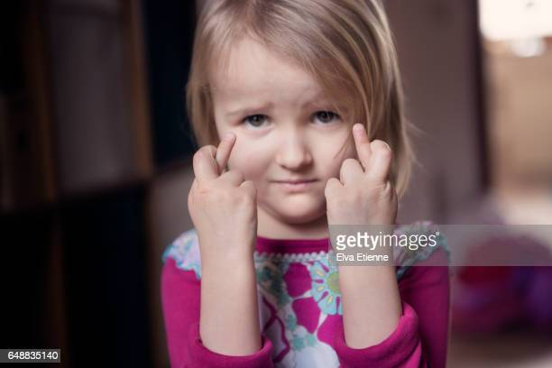 Child with fingers crossed, wishing for luck