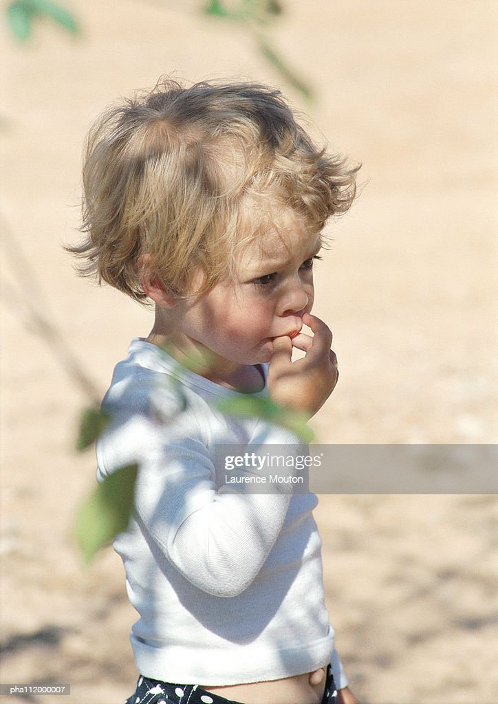 Child with fingers in mouth, tree leaves in foreground : Stock Photo