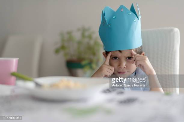 child with foam crown eats macaroons at home. king of home. - reality kings stock pictures, royalty-free photos & images