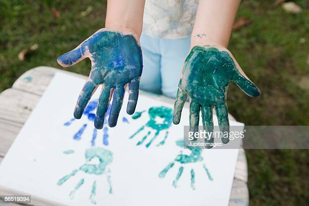 Child with handprint painting and paint on hands