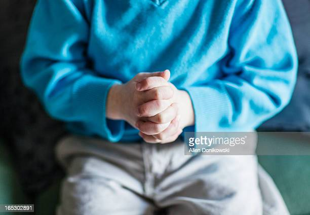child with hands clenched together worrying
