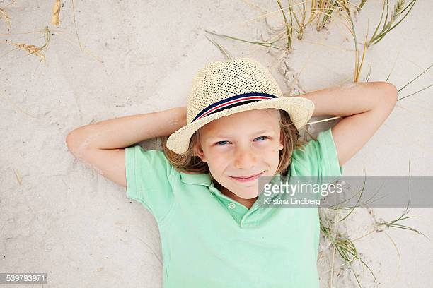 Child with hat lying on the sand looking to camera