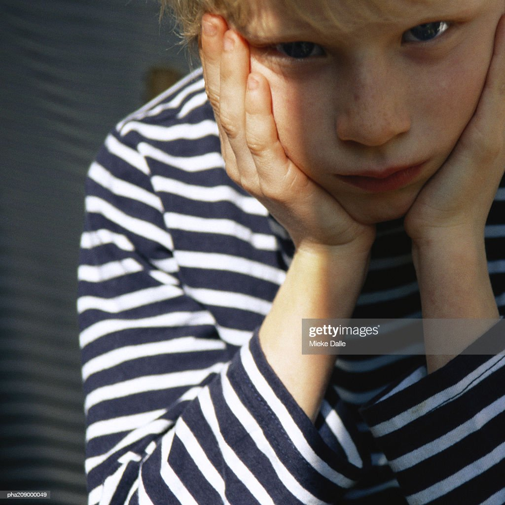 Child with head in hands. : Stockfoto