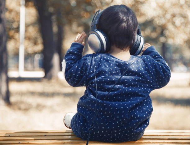 Child with headphones listening music outdoors