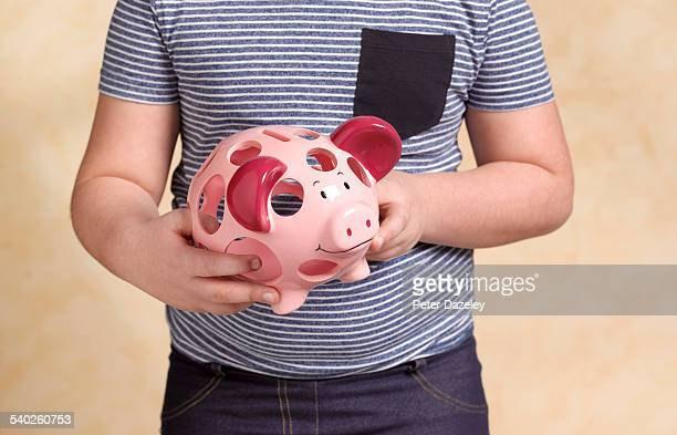 child with holey piggy bank - fat belly girl stock photos and pictures