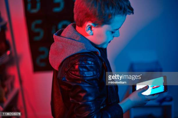 Child with hoodie looks at screen on smart phone at night