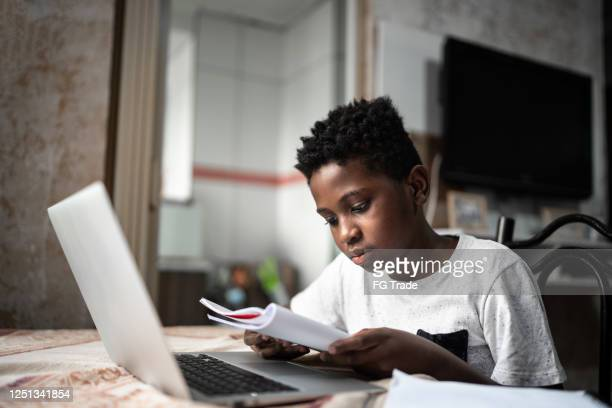 child with laptop on a online class at home - childhood stock pictures, royalty-free photos & images